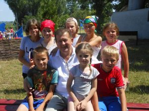 Pastor Savich with children at camp